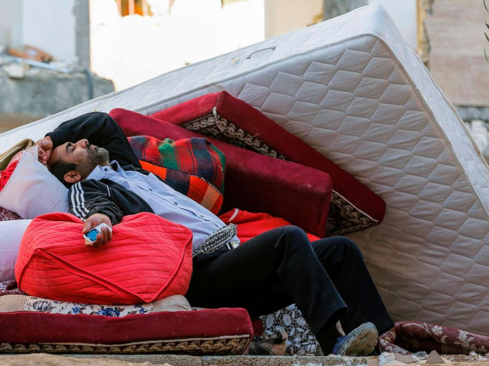 PHOTO: A man lies atop salvaged mattresses and other possessions outside damaged buildings in the town of Sarpol-e Zahab in the western Kermanshah province of Iran on Nov. 14, 2017, following a 7.3 magnitude earthquake two days before.