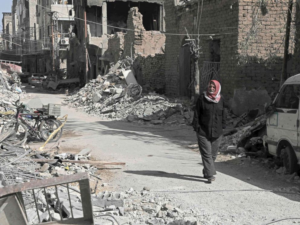 PHOTO: A Syrian man walks down a street past destroyed buildings, March 25, 2018, in Douma, in Eastern Ghouta on the outskirts of the capital Damascus.